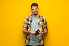Handsome Man Over Yellow Wall Holding A Wallet