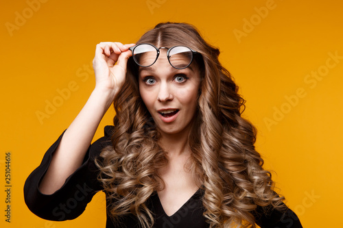 Photo  Handsome surprised girl holding glasses isolated over the yellow background