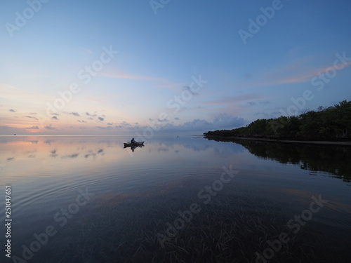 Fotografie, Obraz  Kayaker at sunrise on the perfectly still water of Bear Cut off Key Biscayne, Florida