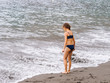 Girl play on a beach in the sea waves and playing on the volcanic sand beach