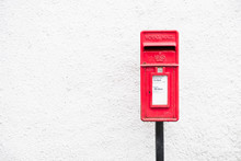 Red Post Mail Box Against Plain White Wall Background