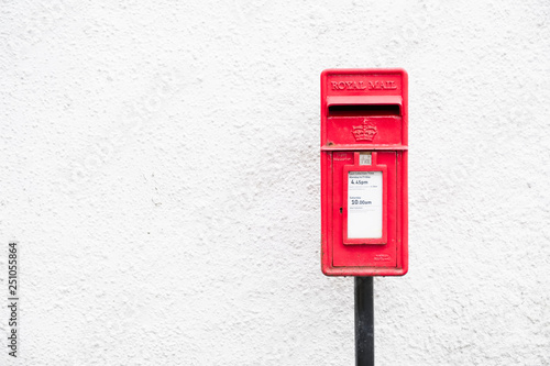 Foto  Red post mail box against plain white wall background