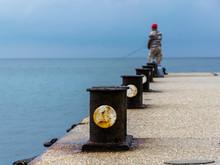 Pier, Bollards And Lone Fisherman