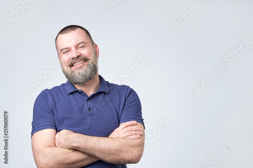 Fotografiet  Mature positive man with beard weairn blue t-shirt holding hand crossed and look