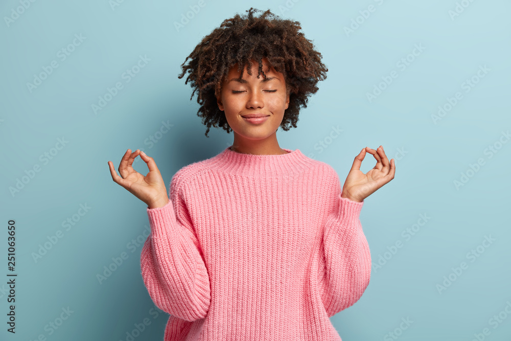 Fototapety, obrazy: People, peace and meditation concept. Calm black young woman practices yoga indoor, shows okay sign with both hands, demonstrates approval, wears pink clothing, isolated over blue background