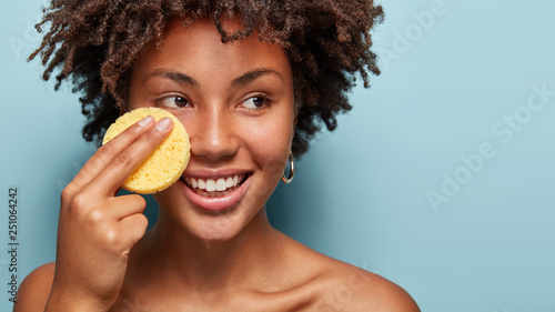 Obraz Beauty and skincare concept. Positive curly African American woman cleans face with exfoliating sponge, looks happlily aside, has pleased expression, removes makeup. Free space on blue wall. - fototapety do salonu
