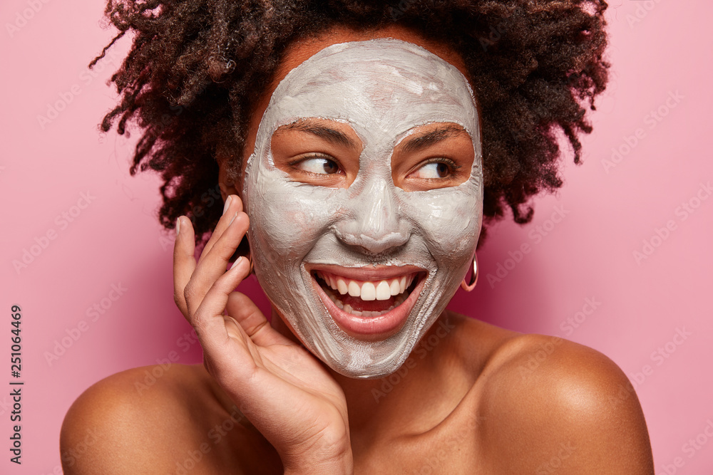 Fototapeta Photo of glad black woman has clay mask, enjoys facial treatments, keeps gaze aside, touches face, has spa therapy, broad smile with white teeth, isolated over pink background. Perfect skin concept