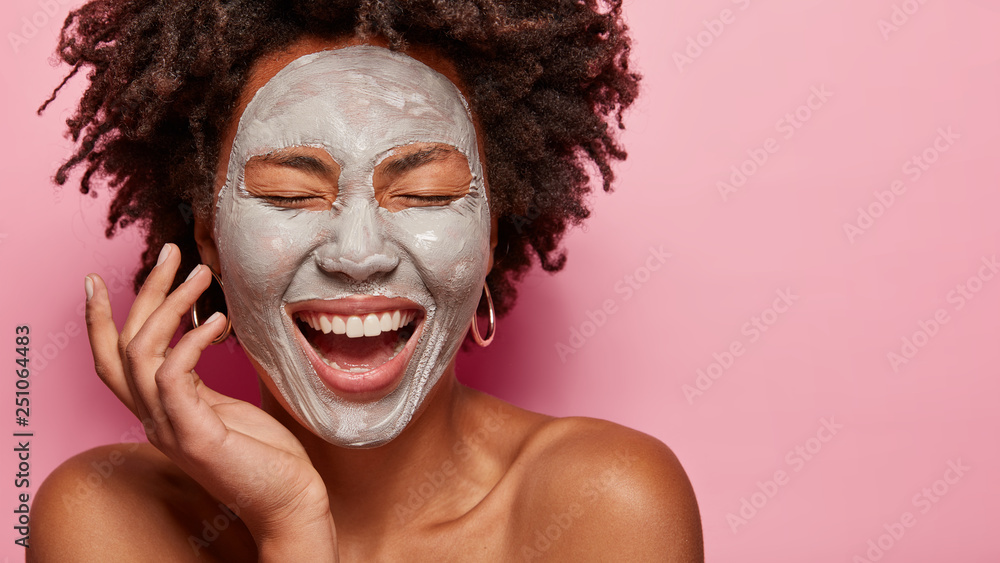 Fototapety, obrazy: Cropped image of cheerful pleased young African American woman has deep cleansing nourishing face mask, shows bare shoulders, isolated over rosy background with blank space for your promotion.