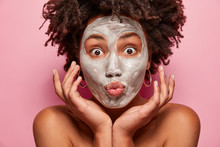 Morning Routine, Cosmetology And Facial Treatments Concept. Topless Attractive Woman With Dark Skin, Curly Hairstyle, Touches Cheeks, Has Bare Shoulders, Isolated Over Pink Background, Cleans Pores