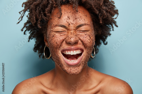 Obraz na plátně Overjoyed woman laughs loudly, cleans face skin with coffee scrub, has natural mask, crisp hair, poses topless against blue background, squints face, wants to have healthy skin