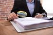 Leinwandbild Motiv Businessman Examining Invoice Through Magnifying Glass