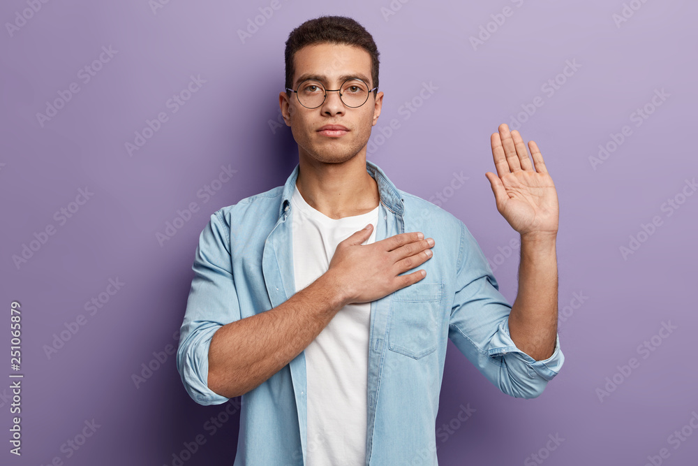 Fototapeta Honest serious hipster guy swears to do something, keeps hand on chest, gestures with palm, promises something, wears spectacles and denim shirt, swears indoor, isolated over purple background