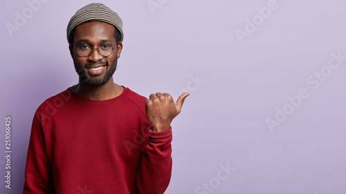Photo Satisfied black guy with stubble, has toothy broad shining smile and white teeth