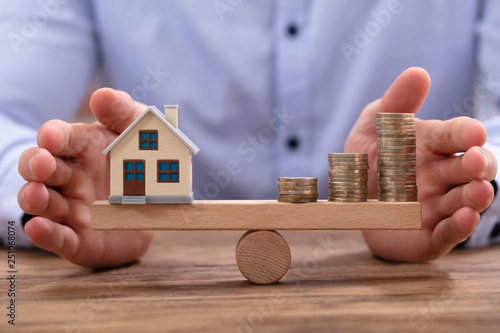 House Model And Golden Coins Balancing On Seesaw Canvas Print