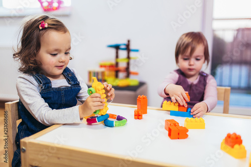 Photo  Children toddlers girls play toys at home, kindergarten or nursery