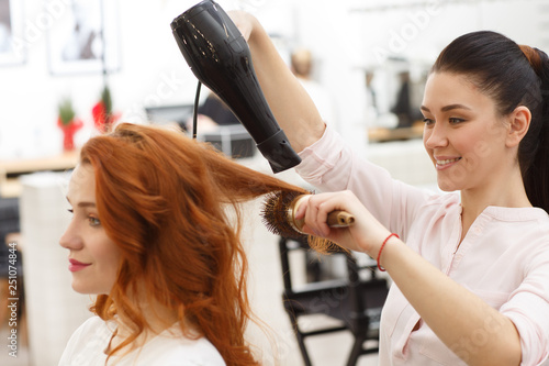 Shot of a cheerful hairdresser blow drying hair of a beautiful young woman, working at her beauty salon Canvas Print