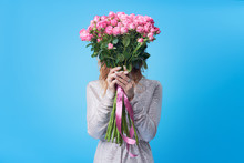 Young Happy Smiling Redhead Woman Holding Bouquet Of Colorful Spring Flowers Isolated On Blue Background. Pink Roses, Festive Bouquet In Honor Of Women's Day On March 8 Or Birthday