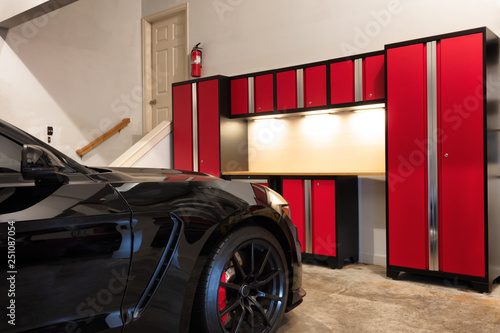 Home garage interior highly organized and clean with parked car Canvas Print