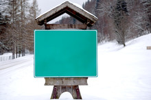 Street Sign Hanging On A  Wooden Panel  That Has The Shape Of A House  At The Exit From A Mountain  Village During Winter.