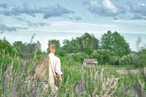 Photo  man in an old world war II uniform in a field among tall wild grasses with a big