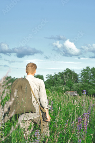 man in an old world war II uniform in a field among tall wild grasses with a big Canvas Print