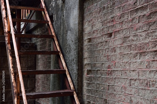 Fotografie, Obraz  錆びた鉄の階段と古いレンガの壁