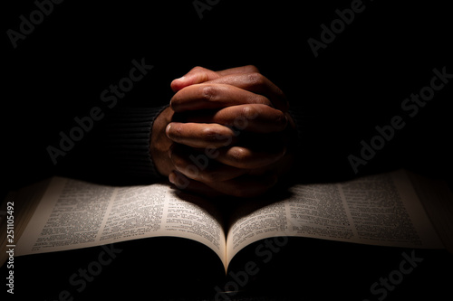 Canvas-taulu African American Man Praying with Hands on Top of the Bible.