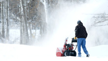 Man Works With A Snow Blower To Remove Newly Fallen Snow From Driveway After Storm In Minnesota.