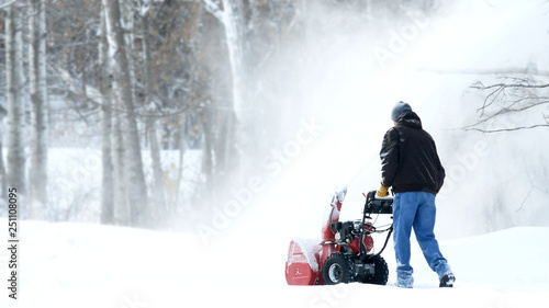 Photo Man works with a snow blower to remove newly fallen snow from driveway after storm in Minnesota
