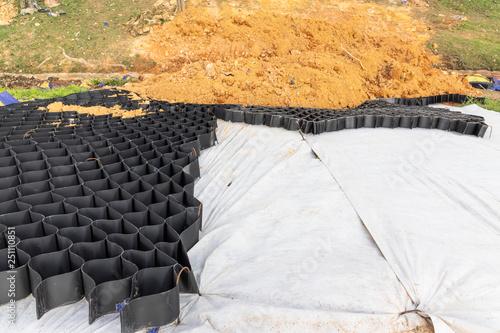 Obraz na plátně Slope erosion control grids, sheets and earth on steep slope