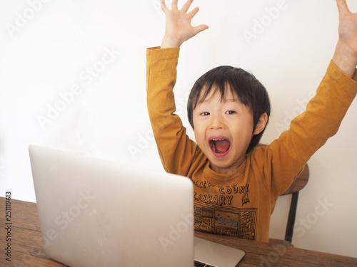 Valokuva  パソコンの前でバンザイする男の子