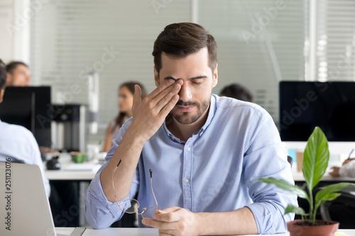 Fotografia  Office worker taking off glasses rubbing tired eyes