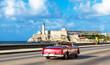 Amerikanischer purpur farbener Cabriolet Oldtimer auf dem berühmten Malecon und im Hintergrund die Festung Castillo de los Tres Reyes del Morro in Havanna Kuba - Serie Kuba Reportage