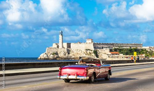 Photo Stands Havana Amerikanischer purpur farbener Cabriolet Oldtimer auf dem berühmten Malecon und im Hintergrund die Festung Castillo de los Tres Reyes del Morro in Havanna Kuba - Serie Kuba Reportage