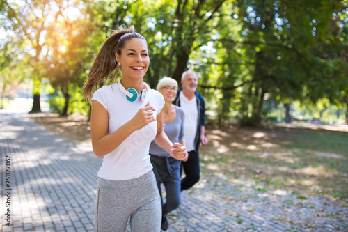 Poster Jogging Senior man and woman and young female instructor workout on fresh air. Outdoor activities, healthy lifestyle, strong bodies, fit figures. Stylish, modern sportswear. Different generations