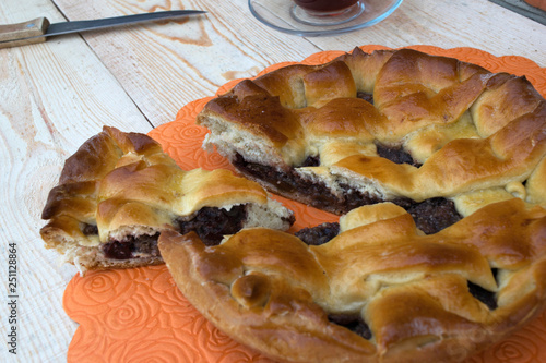 Fotografia  a pie, a slice of apple pie with cherry and walnuts, a knife and a cup of tea on