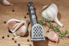 Hand Garlic Press Surrounded By Garlic