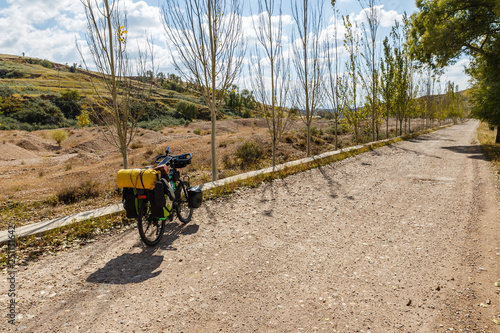 Fotografie, Obraz  traveler's bike with bags stands on an empty gravel road