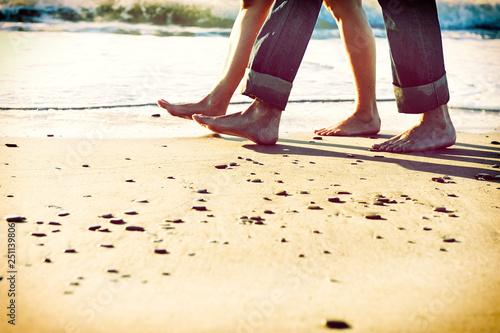 Canvas Print Pies descalzos de pareja paseando por la orilla de la playa al amanecer