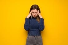 Teenager Girl Over Yellow Wall With Headache
