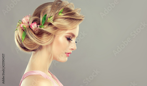 Beautiful model girl  with elegant hairstyle and rose flowers in a plait . Woman with fashion  spring hair.