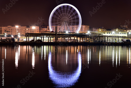Fotografía  View of Malaga city and giant wheel from harbour, Malaga, Spain