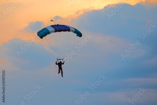 Fotografie, Obraz  Parachutist falling from the sky in evening sunset dramatic sky