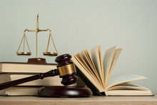 Law Concept. Wooden Judge Gavel With Law Books ,scales Of Justice On Table In A Courtroom Or Enforcement Office.