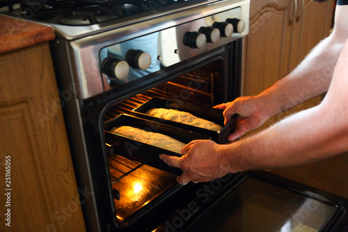 Man taking baked loafs of bread out of the oven. Beaking bread at home