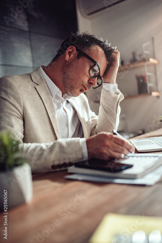 Photographie Businessman scratching head and writing notes in note pad