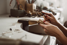 Master's Hands. Side View Of A Female Jeweler Hands Creating A Silver Ring At Her Workbench. Making Accessories