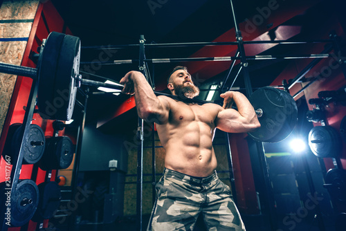 Fotografie, Obraz  Low angle view of muscular sexy shirtless man in military shirts lifting dumbbells in the gym at night