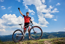 Happy Professional Sportsman Cyclist Standing With Cross Country Bicycle On A Hill, Rasing Hand, Against Blue Sky With Clouds On Summer Sunny Day. Outdoor Sport, Success And Life Goals Concept