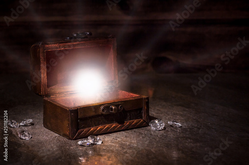 Photo  pen old pirate chest and whte light from it, brilliants, treausres in chest, pir